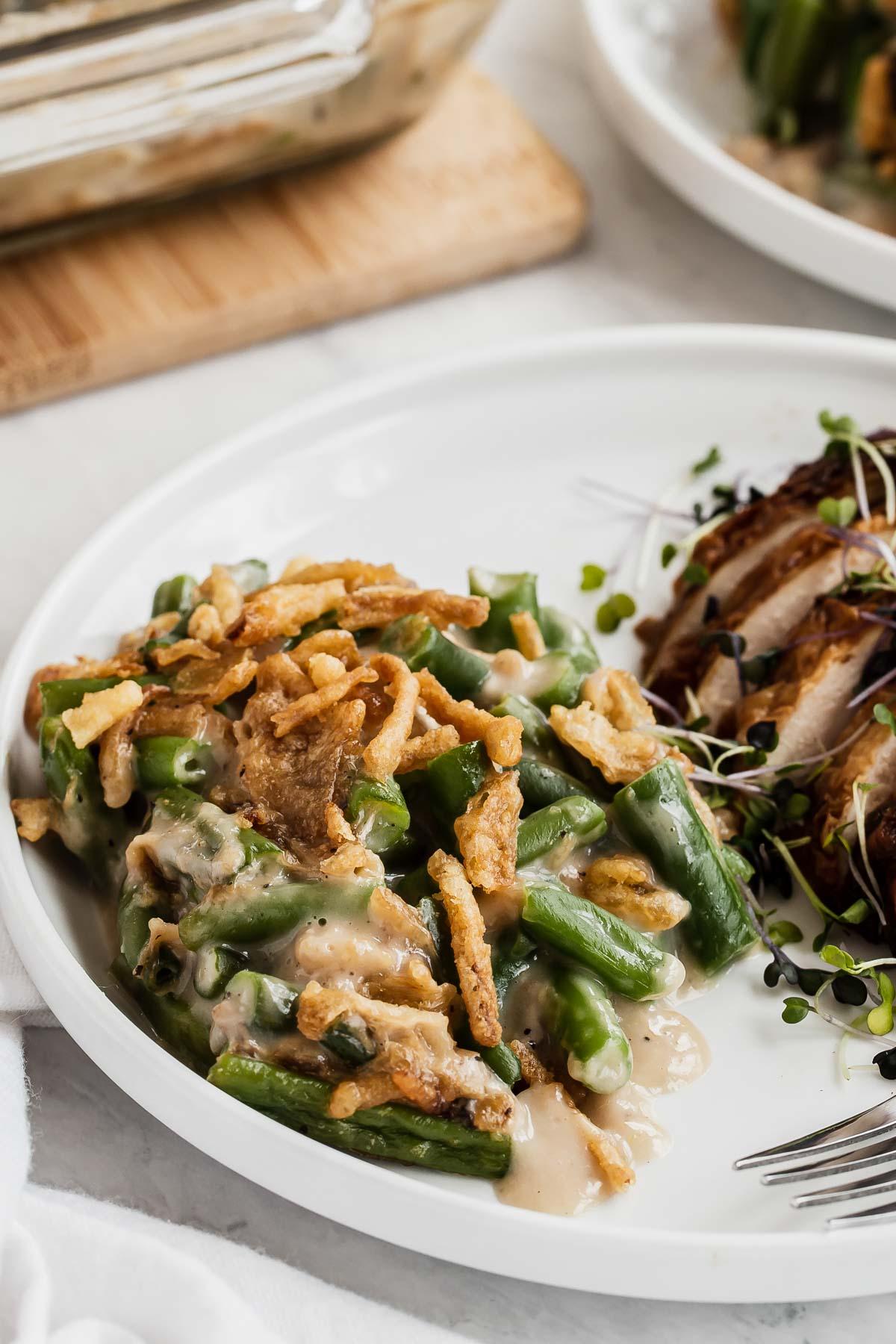 Green bean casserole next to sliced turkey on plate.