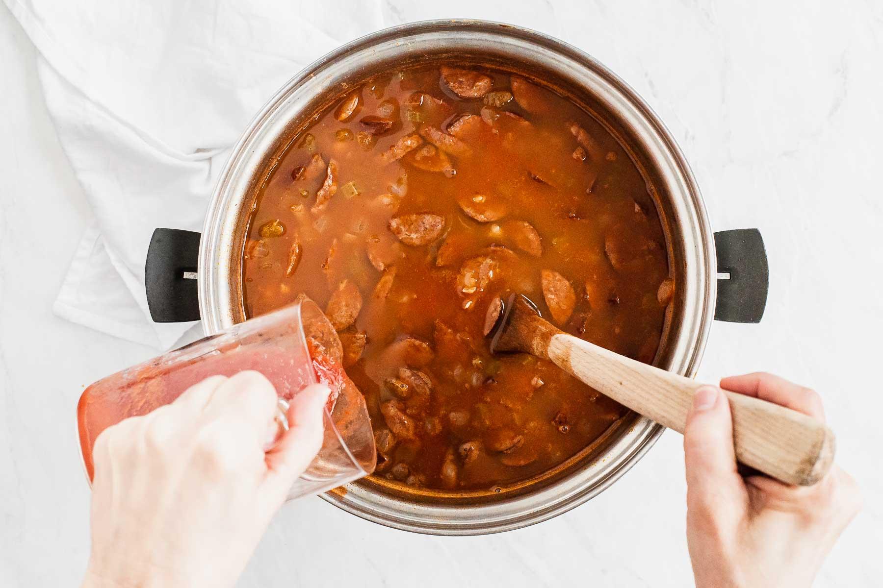 Pouring tomato puree into a soup pot.