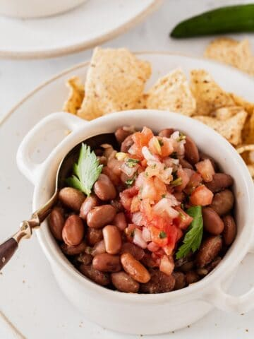Pinto beans with pico de gallo in white bowl and chips on side.