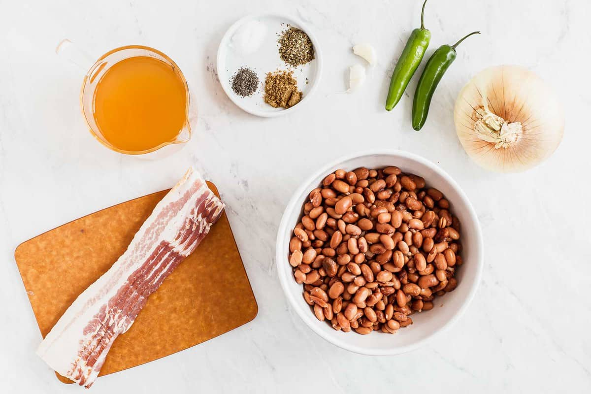 Ingredients for charro beans on white table.