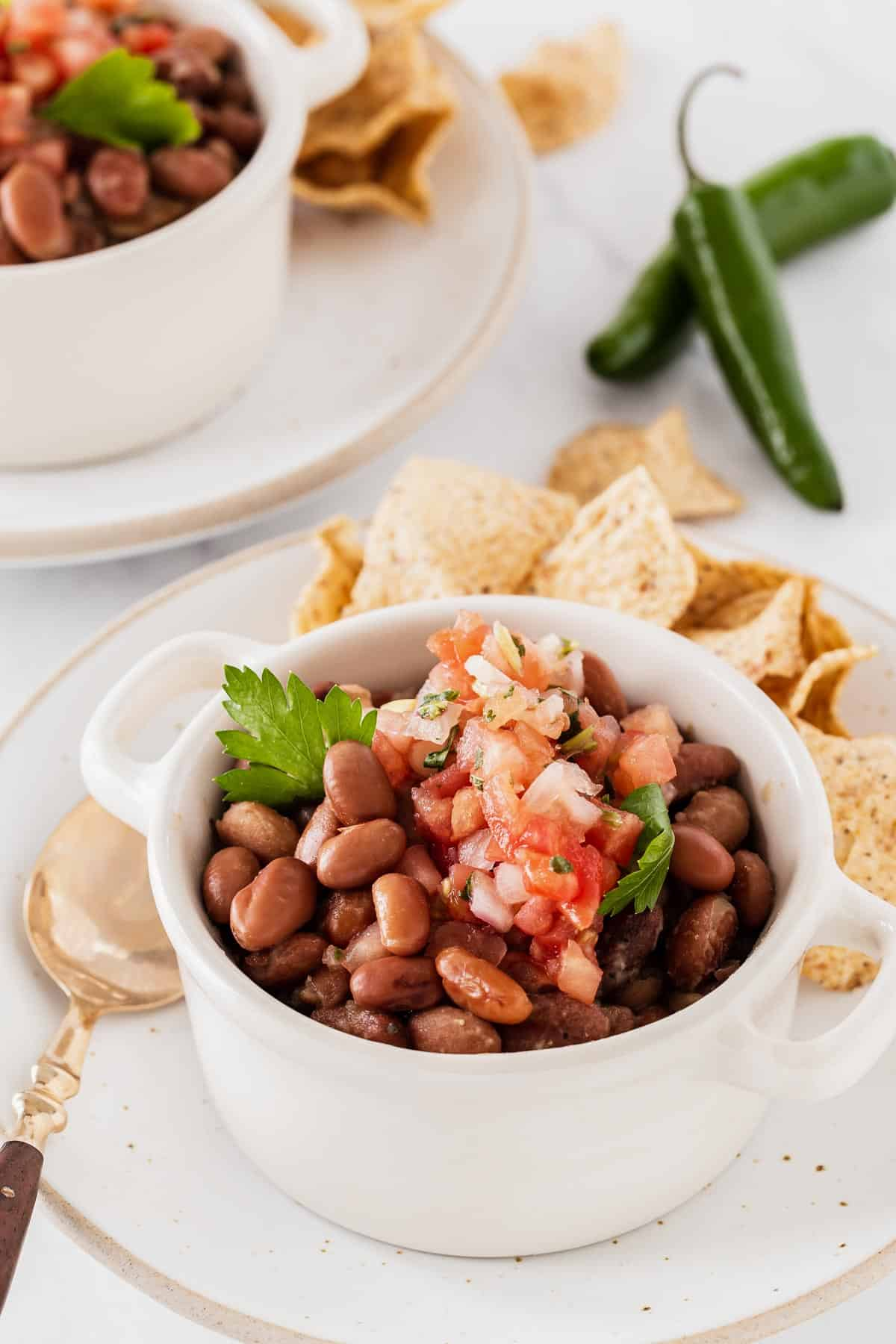 Charro beans in white bowl with chips and jalapeños.
