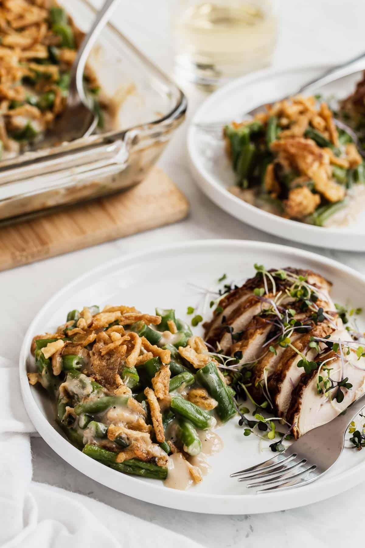 Green bean casserole next to Thanksgiving turkey on two plates.