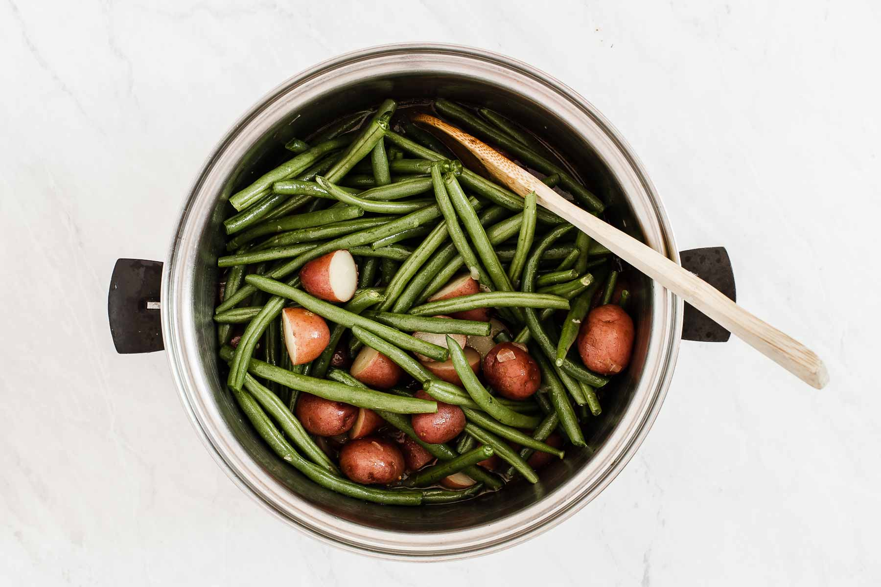 Pot of green beans and potatoes cooking together with wooden spoon.