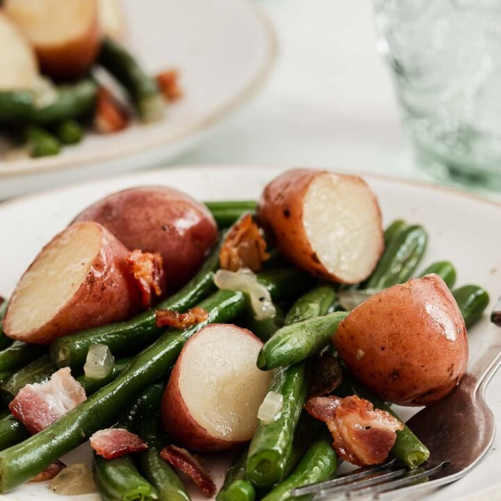 White plate with sautéed green beans and red new potatoes.