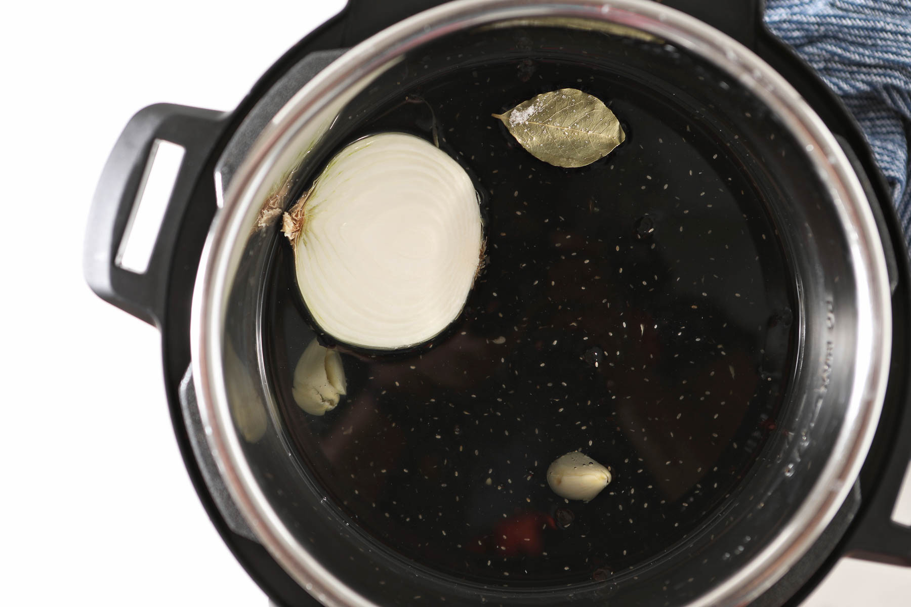 Instant pot with onion, garlic and bay leaf floating in water.