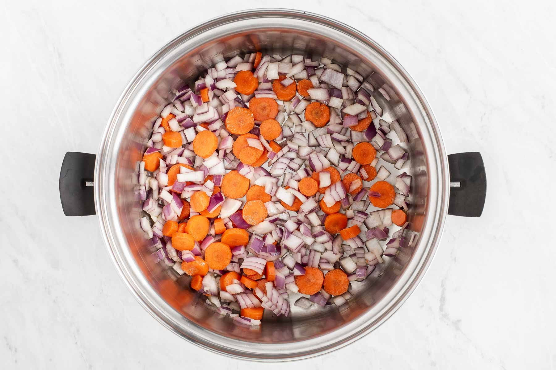 Diced red onion and carrots in a soup pot.