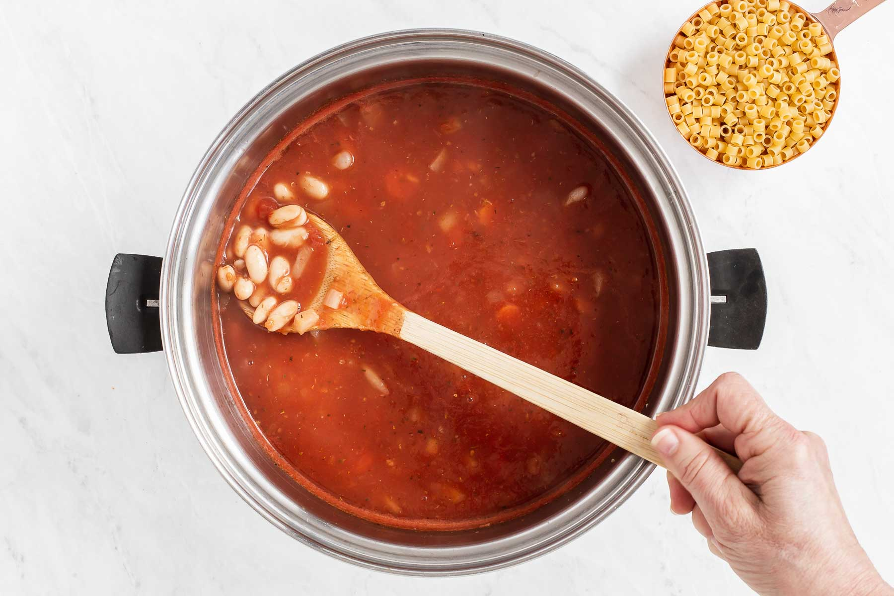 Red tomato soup simmer with spoonful of white beans.