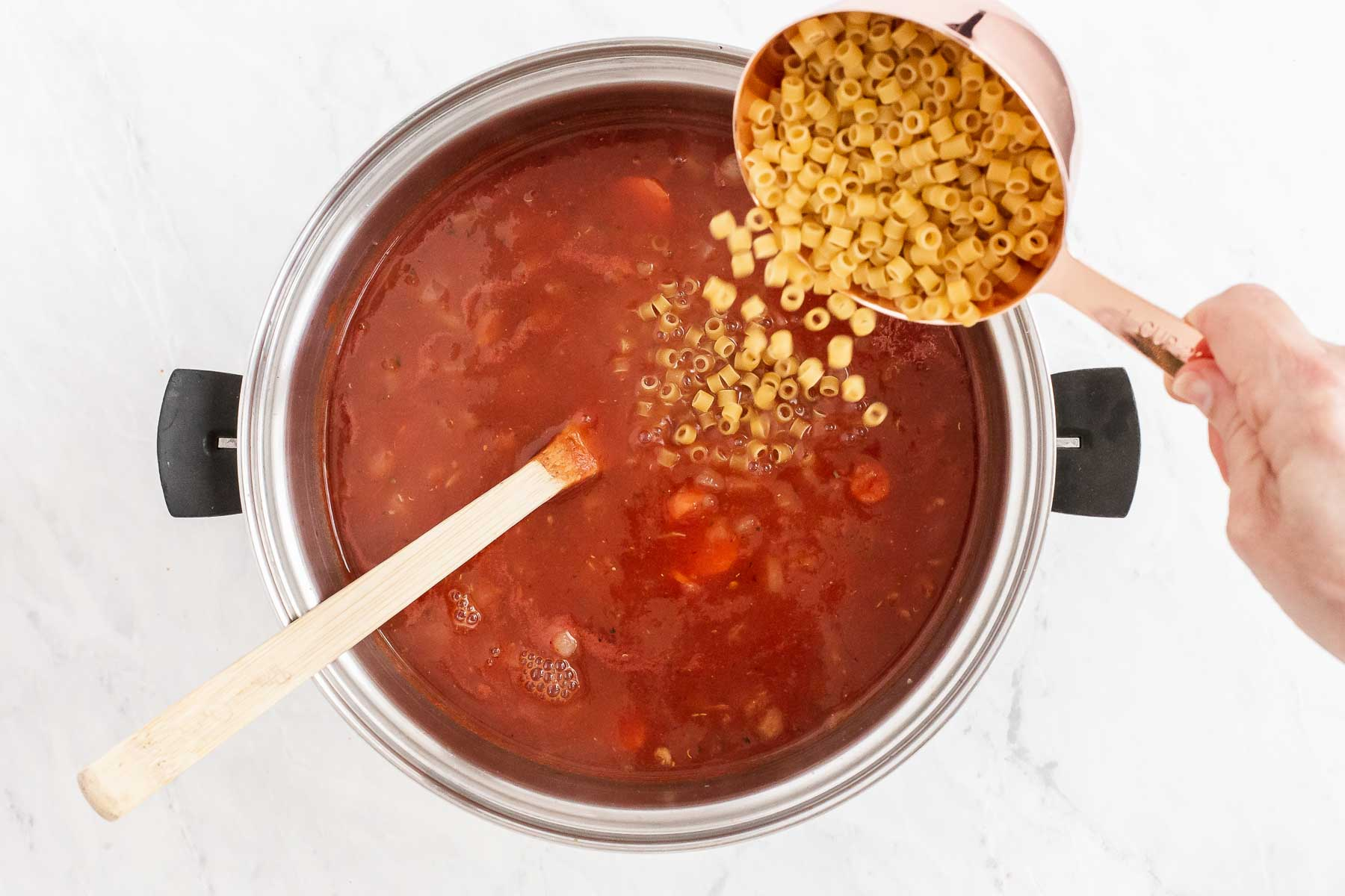 Pouring pasta into red tomato soup.