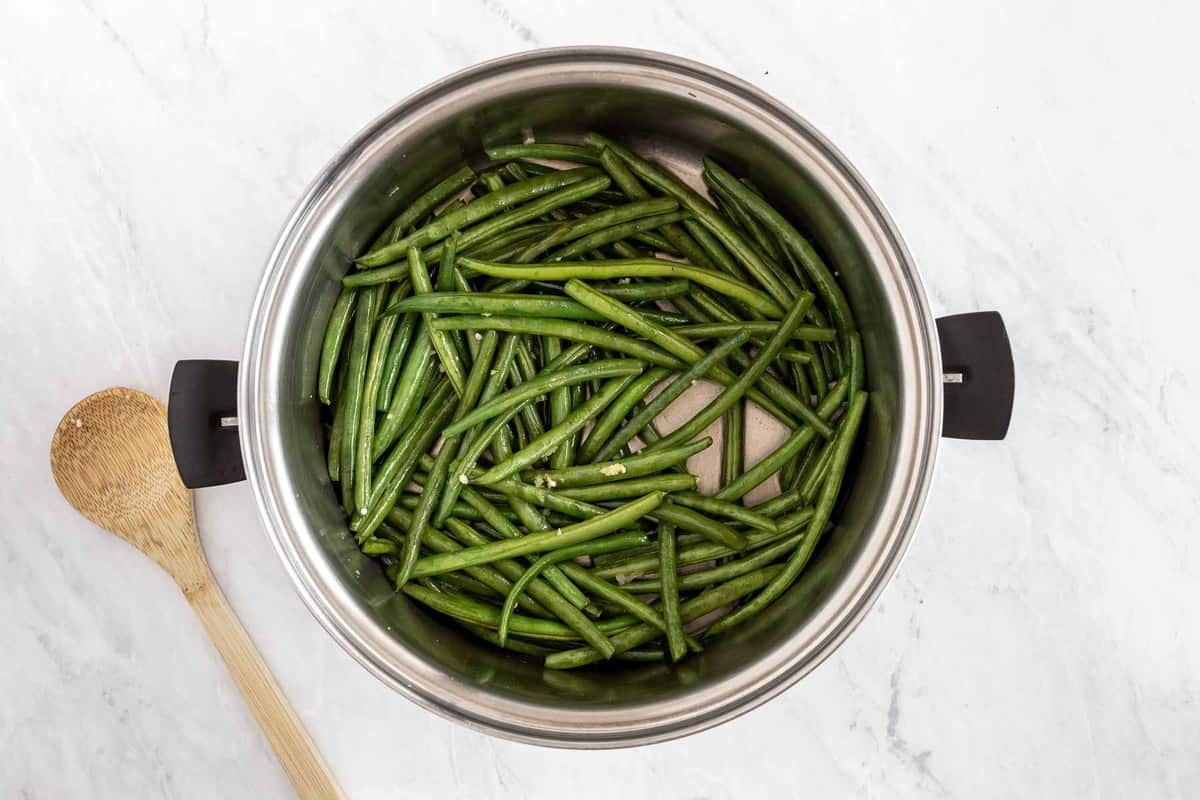 Green beans in a stock pot with wooden spoon.