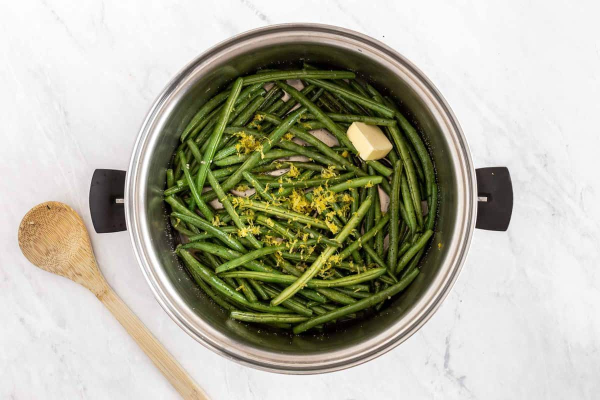 Green beans topped with lemon zest and a pat of butter.