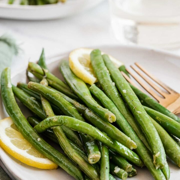 Sauteed green beans on a plate with lemon slices.