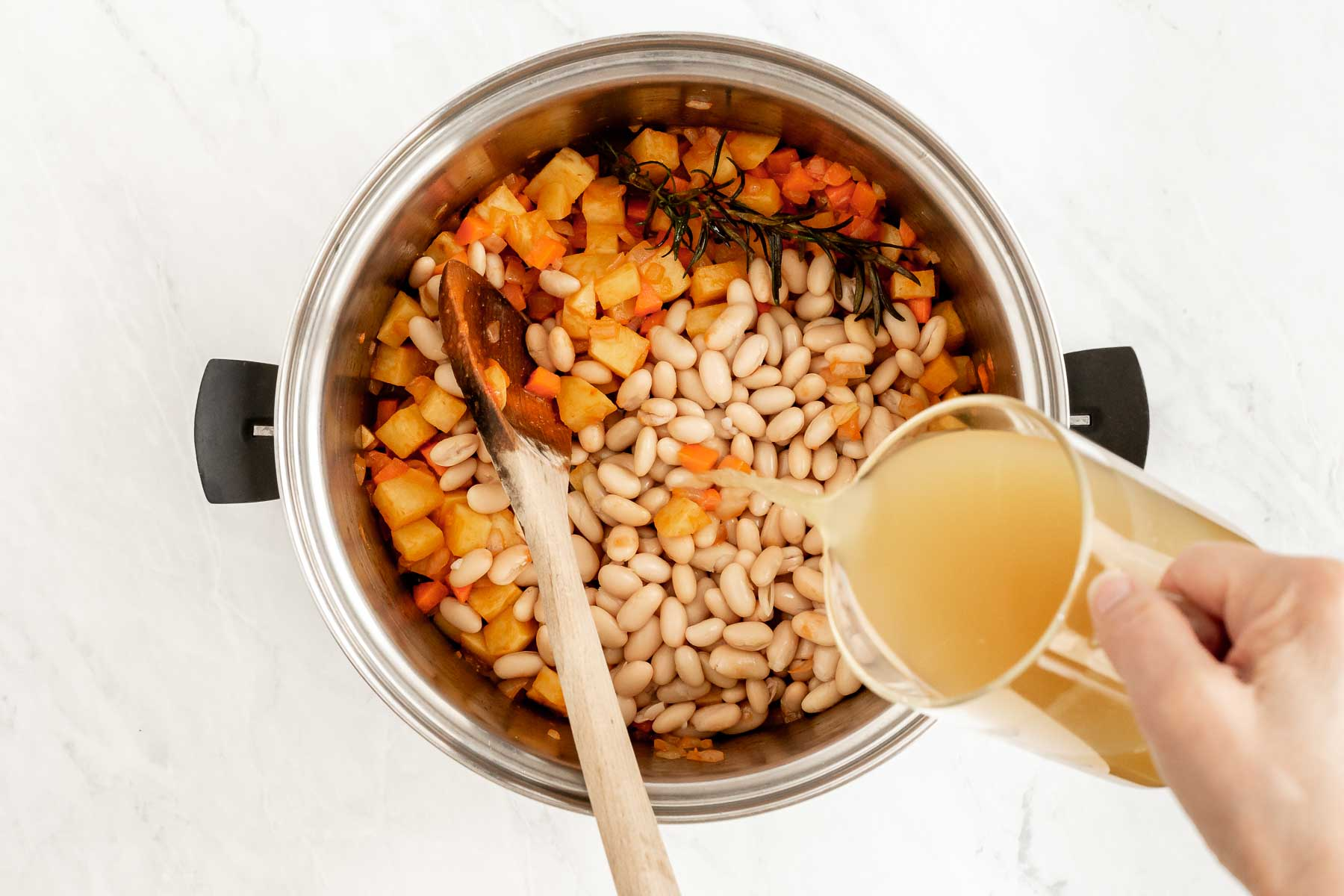 Pouring chicken broth into a soup pot with vegetables.