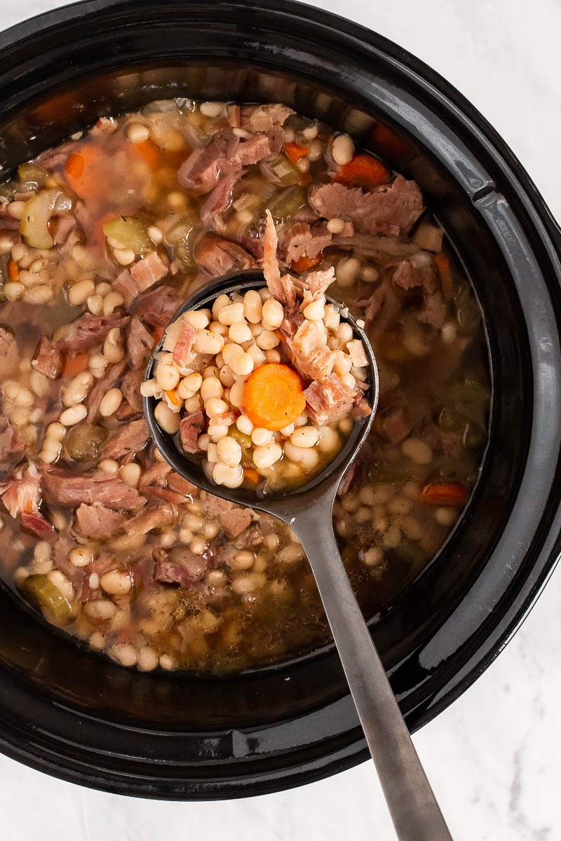 Spoon removing crockpot ham and beans.
