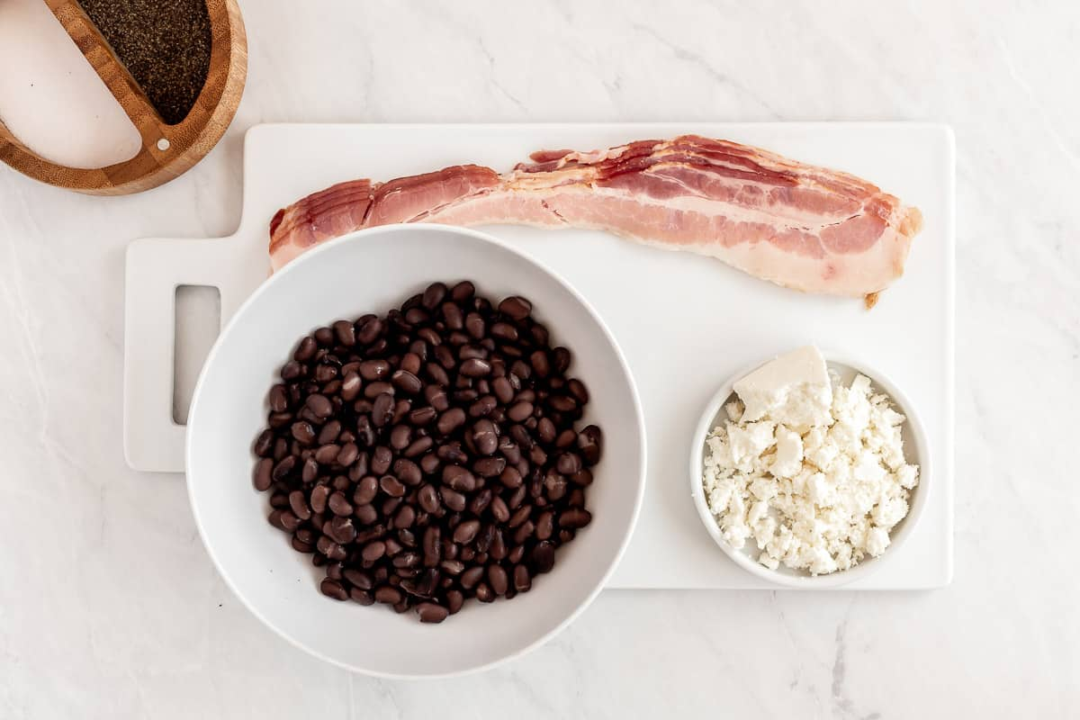Bowl of beans, bacon, and cotija cheese.