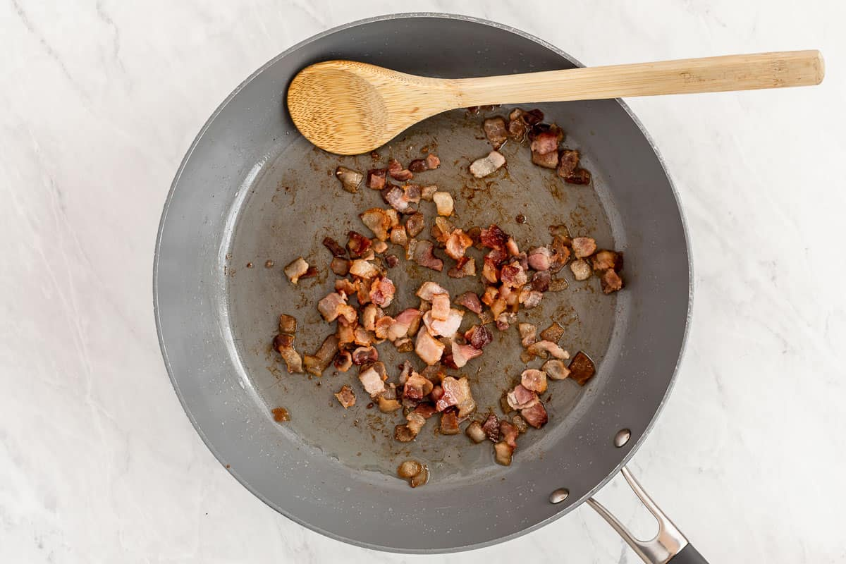 Bacon frying in a skillet with wooden spoon.