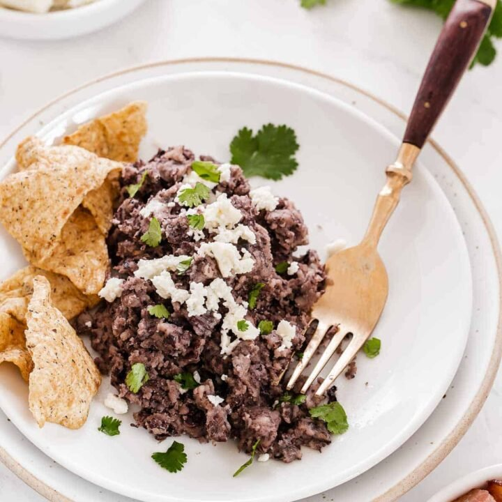 White plate with refried black beans and chips.