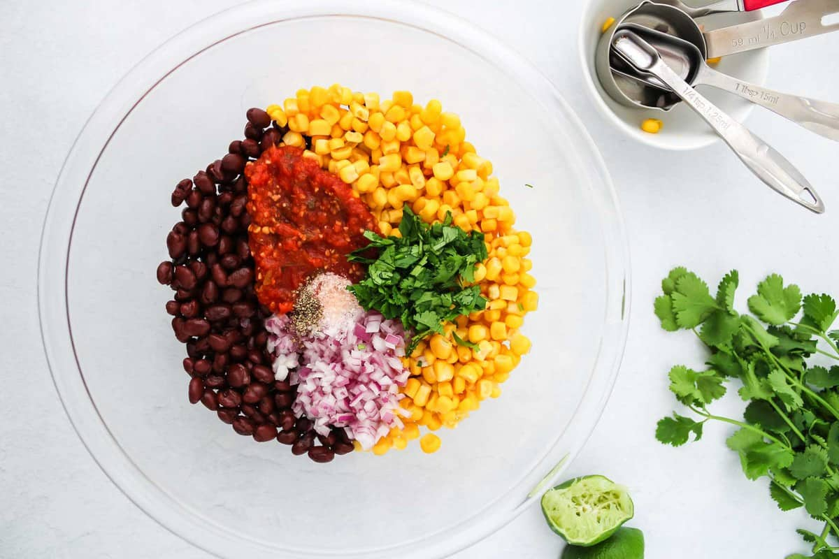 Black beans, corn, and salsa ingredients in a clear bowl.