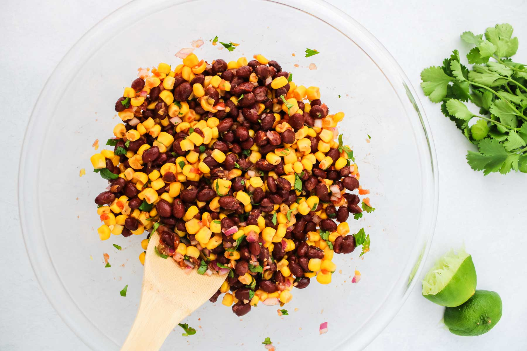 Homemade black bean and corn salsa in clear bowl with cilantro and limes.
