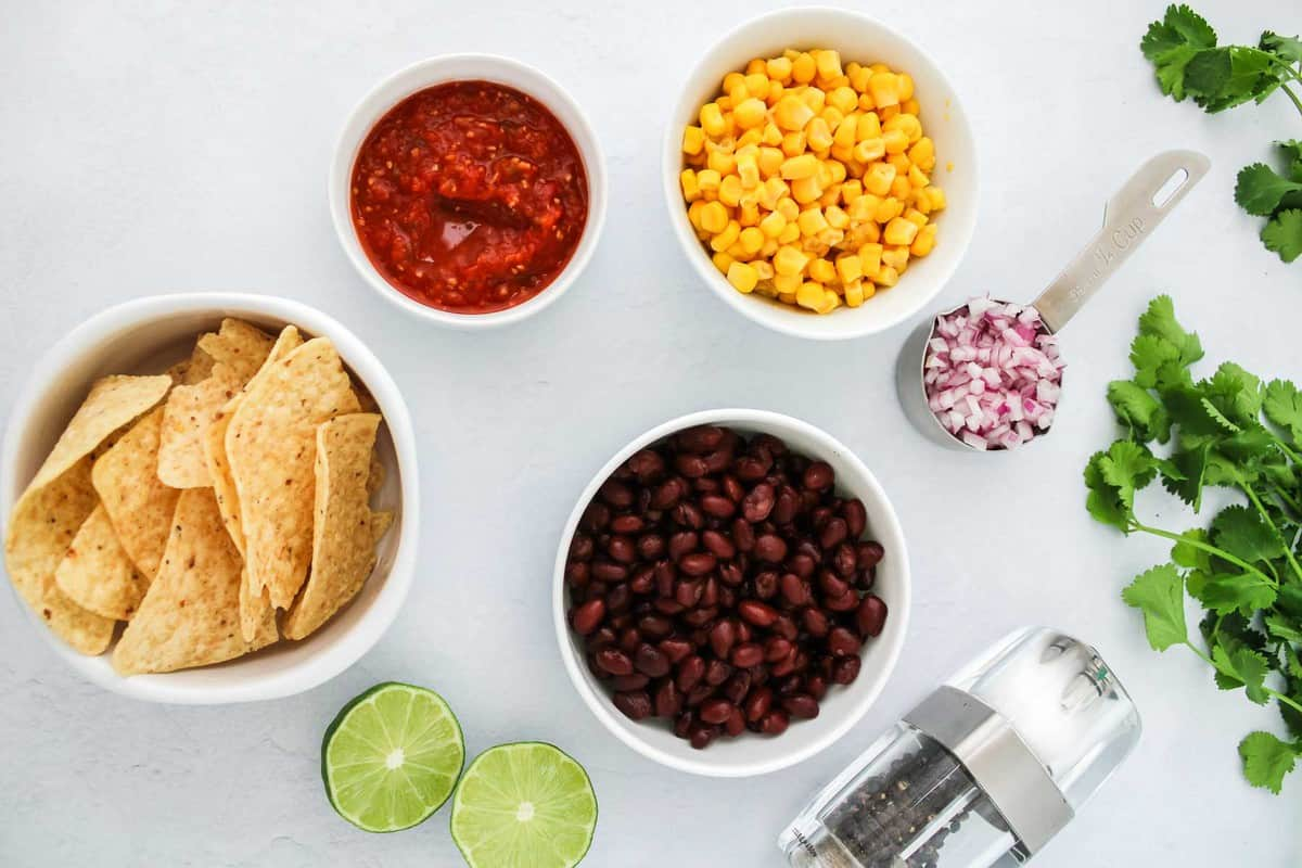 Ingredients for black bean and corn salsa on white table.