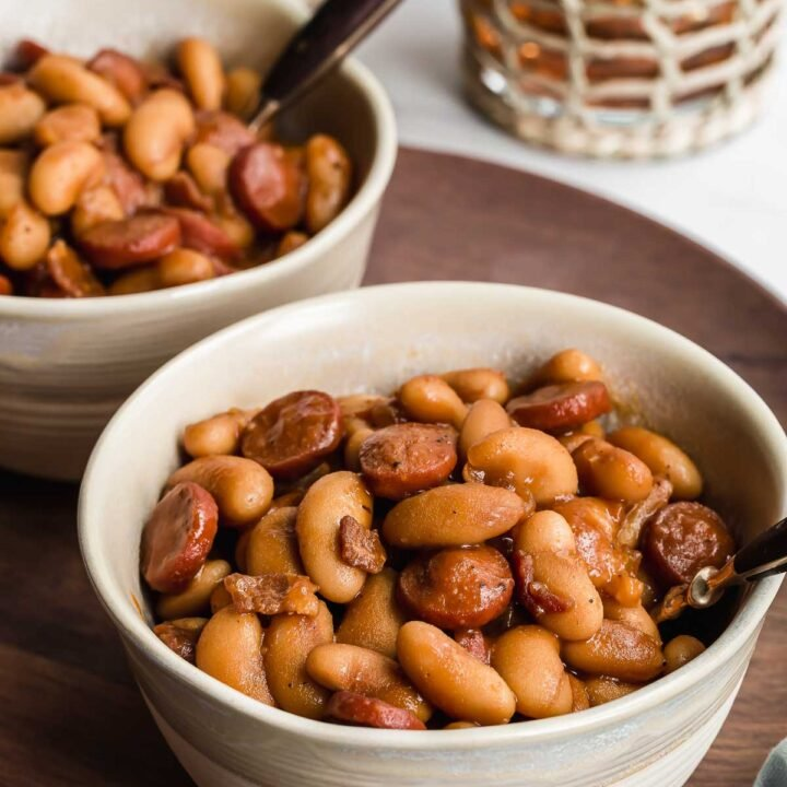 Pork and beans in white bowls with spoon.