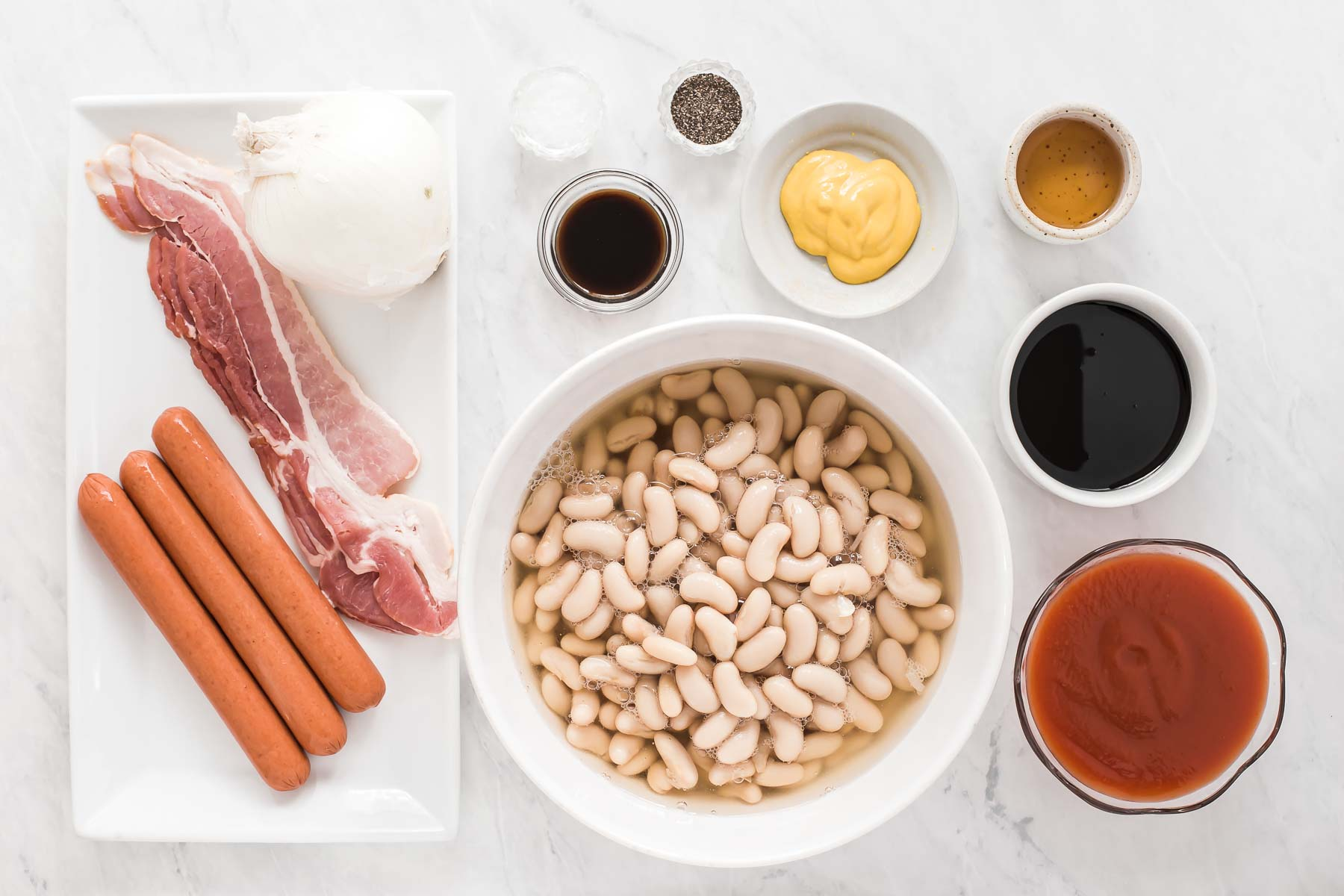 Ingredients for pork and beans on white table.