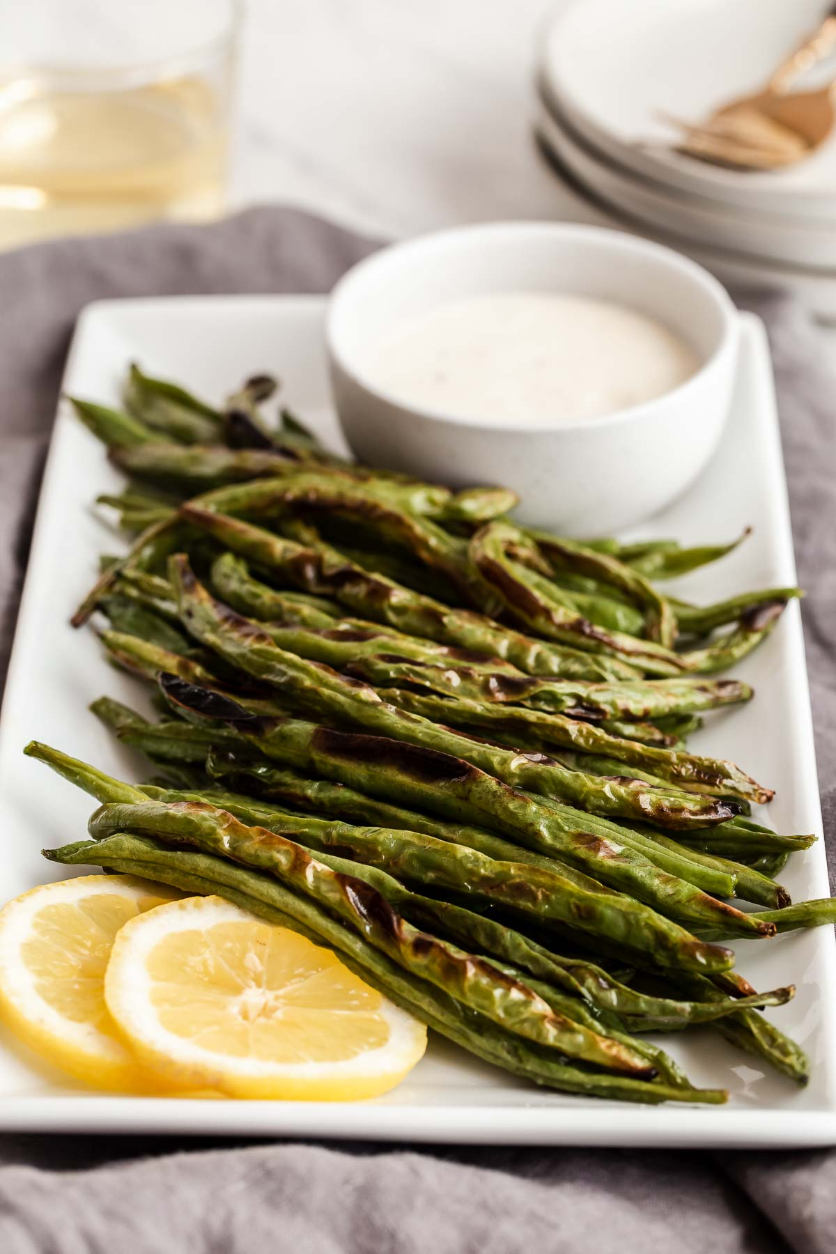 Roasted green beans with ranch on the side.