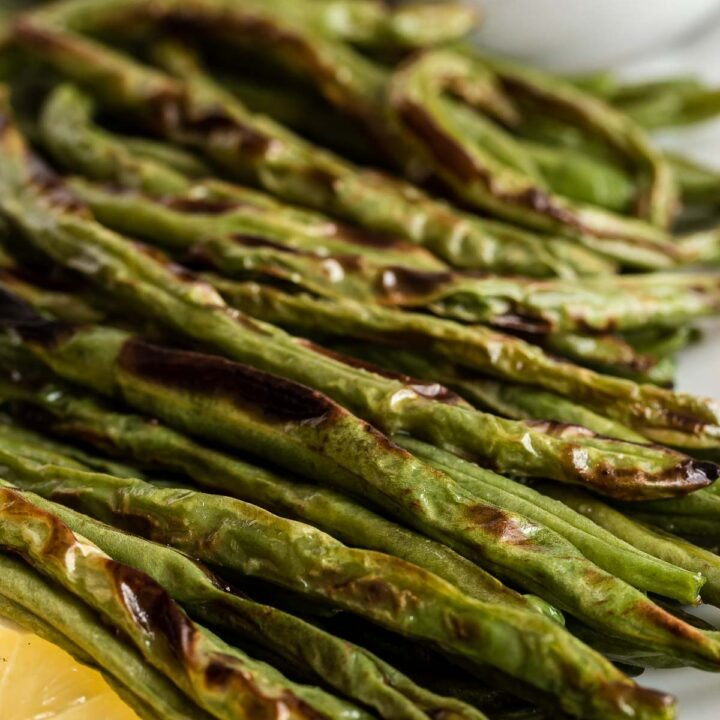 Roasted green beans on a white plate with lemon slice.