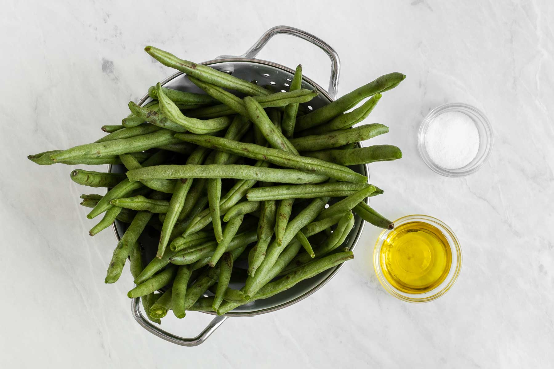 Raw green beans in colander with olive oil and salt on side.