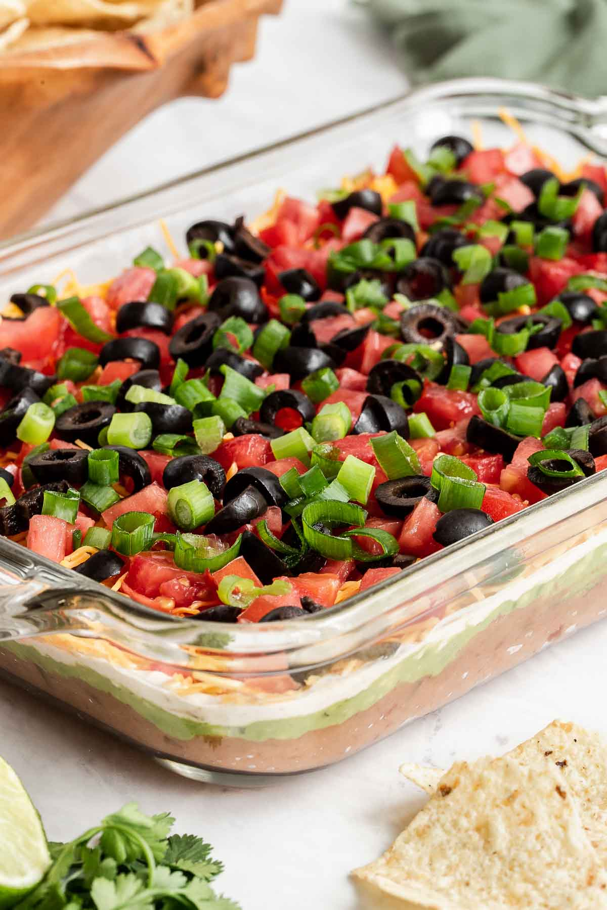 7 layer bean dip in a clear glass dish.