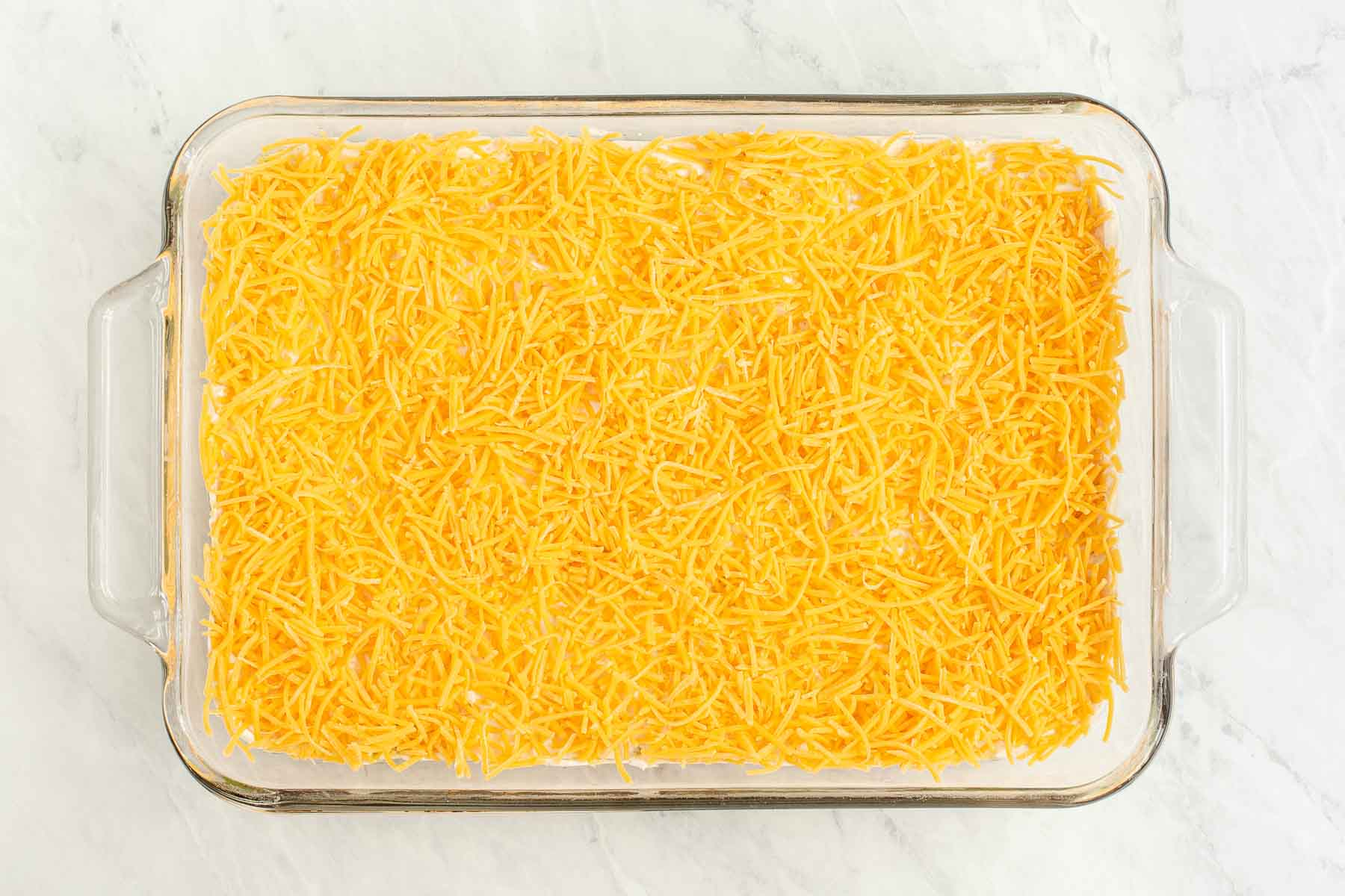 Grated cheddar over sour cream in a casserole dish.