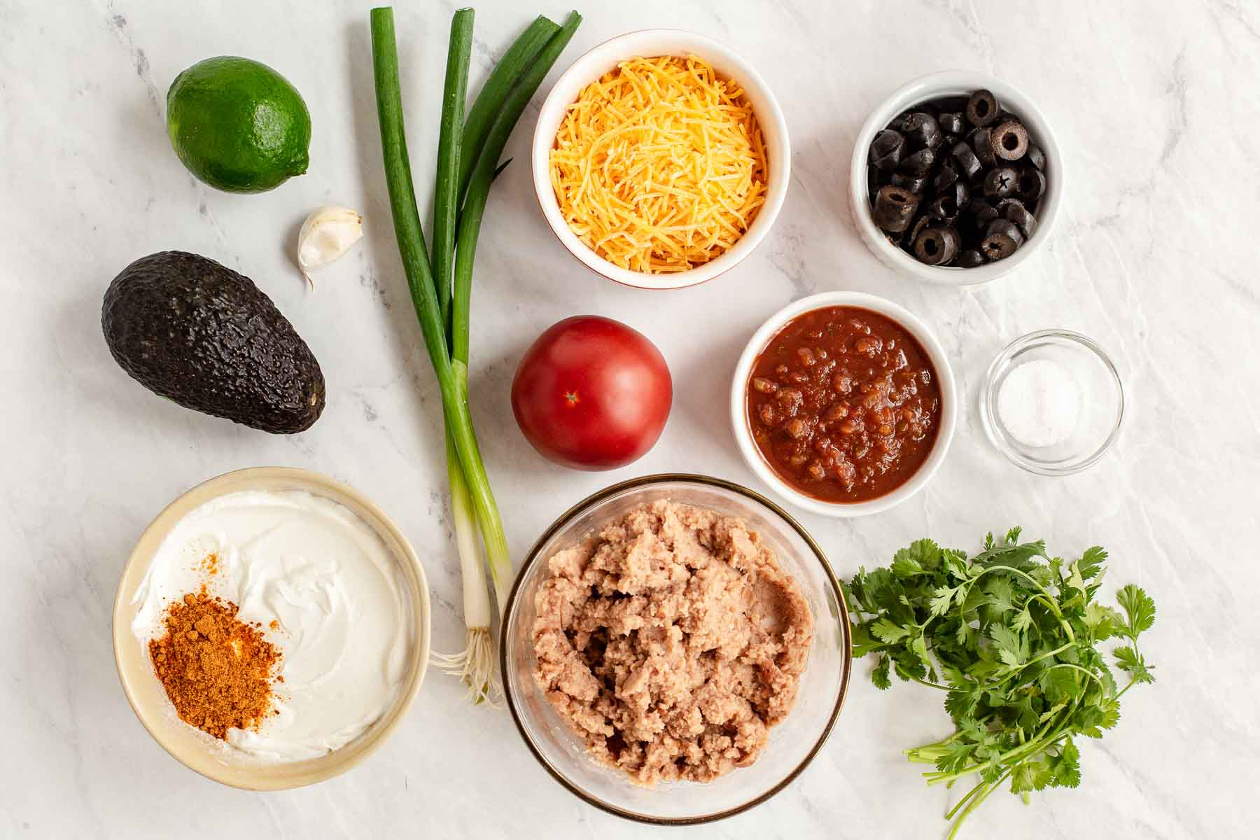 Ingredients in small bowls for making seven layer dip.
