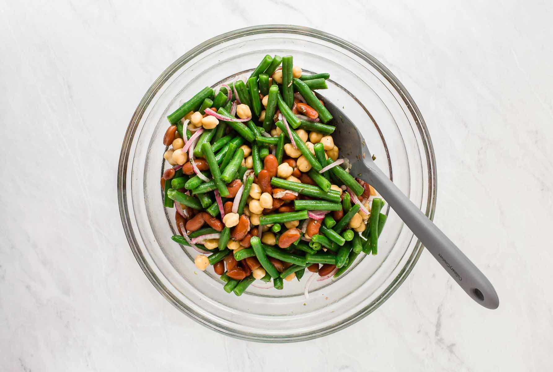 3 bean salad in glass bowl with grey spatula