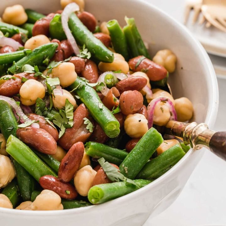 White bowl of three bean salad with serving fork.