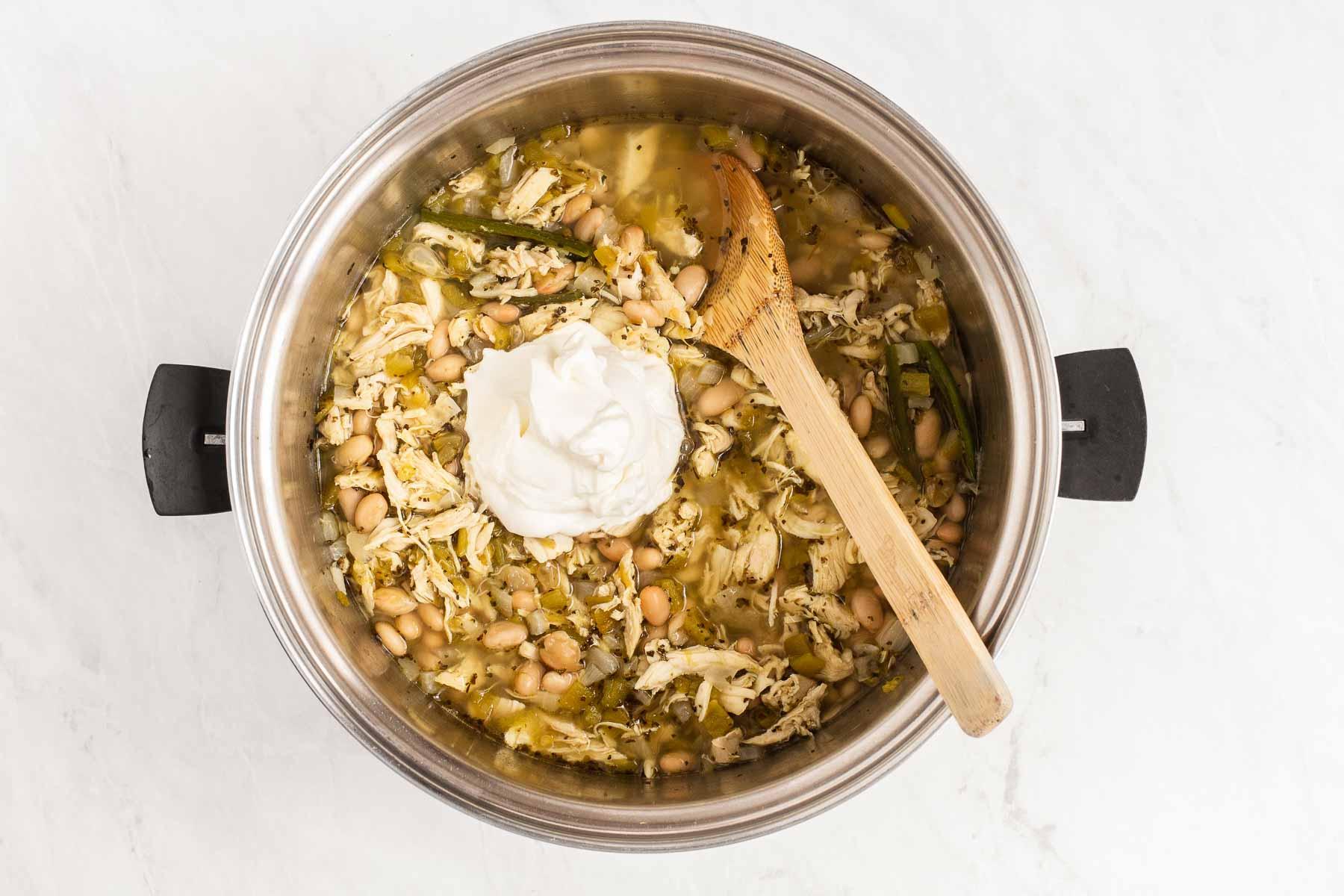 Sour cream in a pot of white chili.