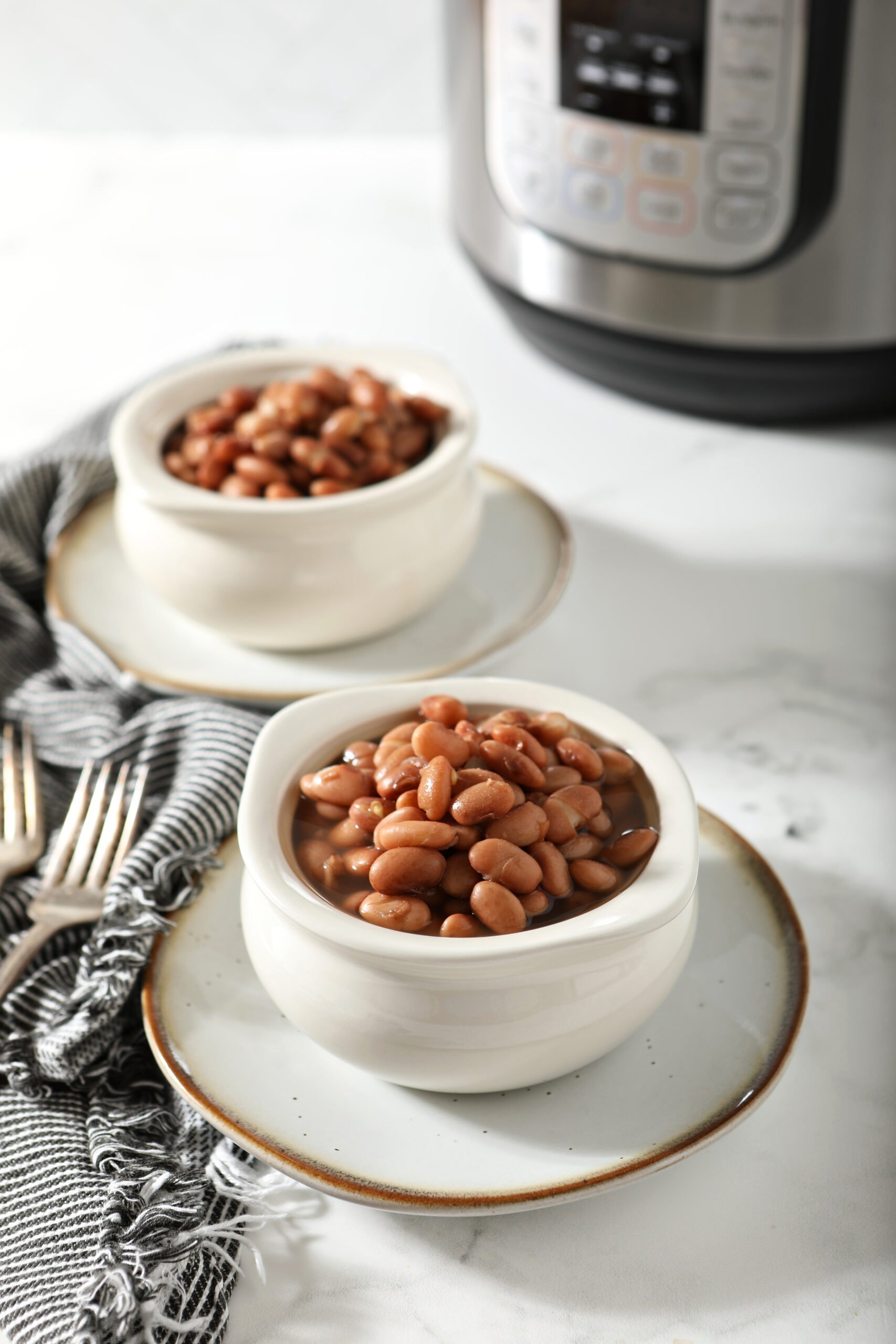 Two white bowls of beans with instant pot in the background.