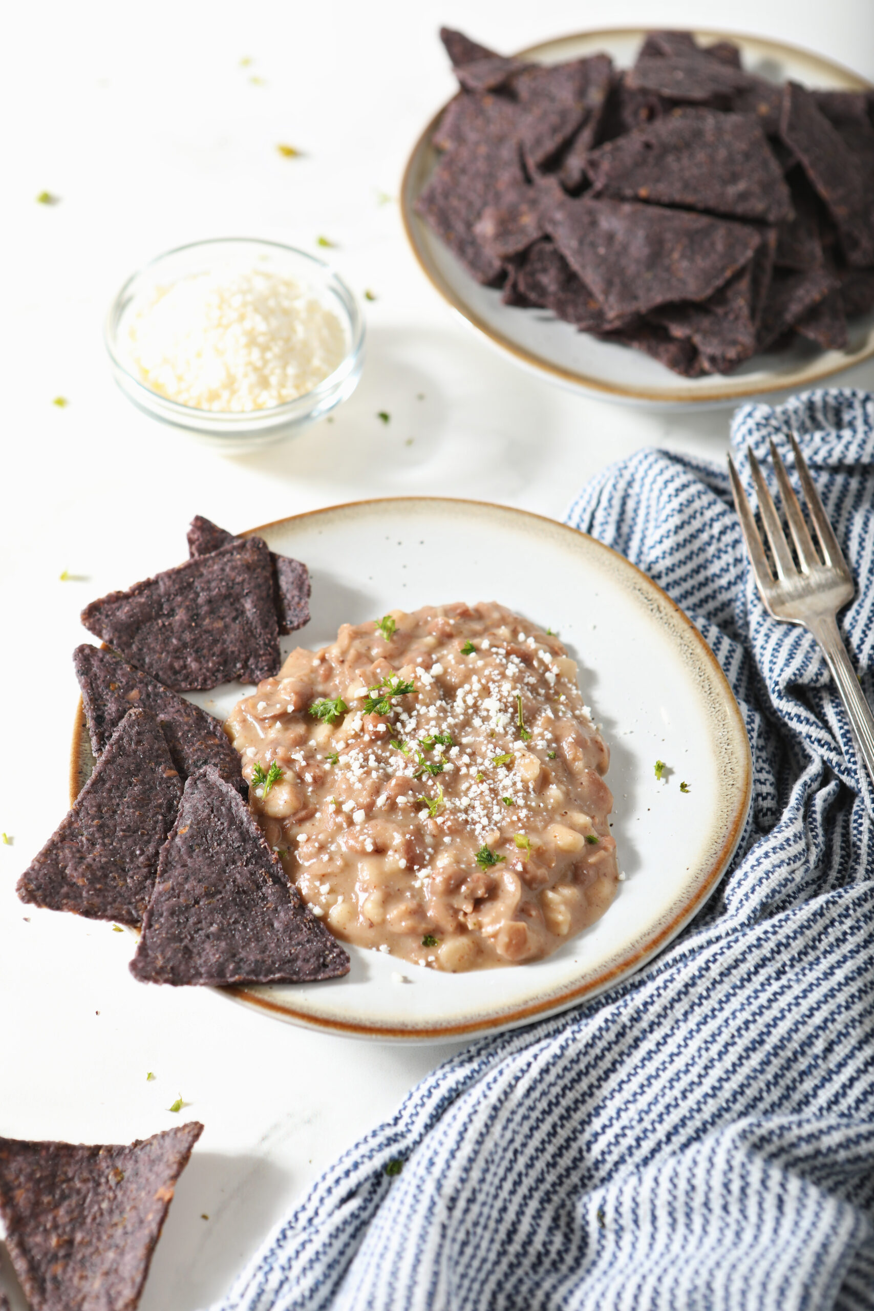Refried beans on plate with cilantro and blue corn tortilla chips.