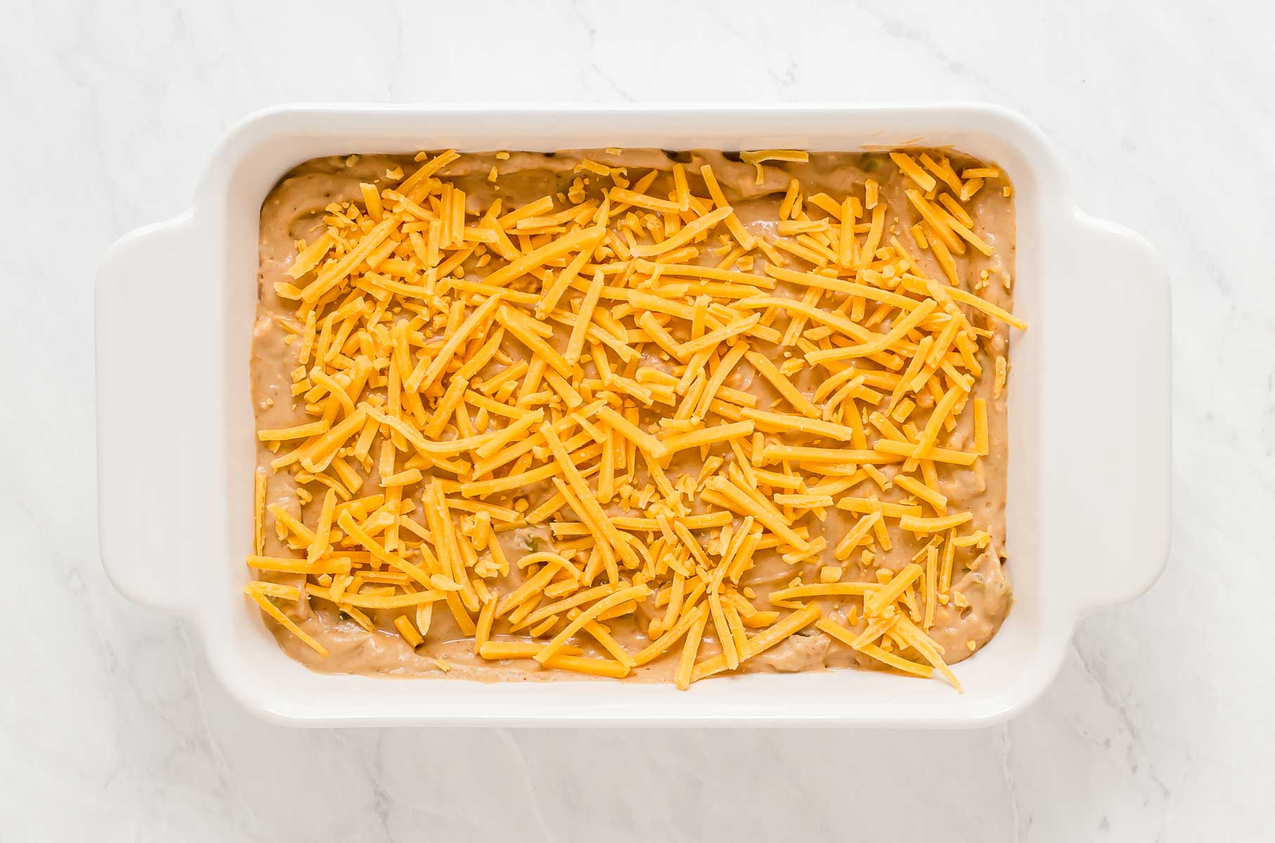 Bean dip with shredded cheddar on top, before going in the oven.