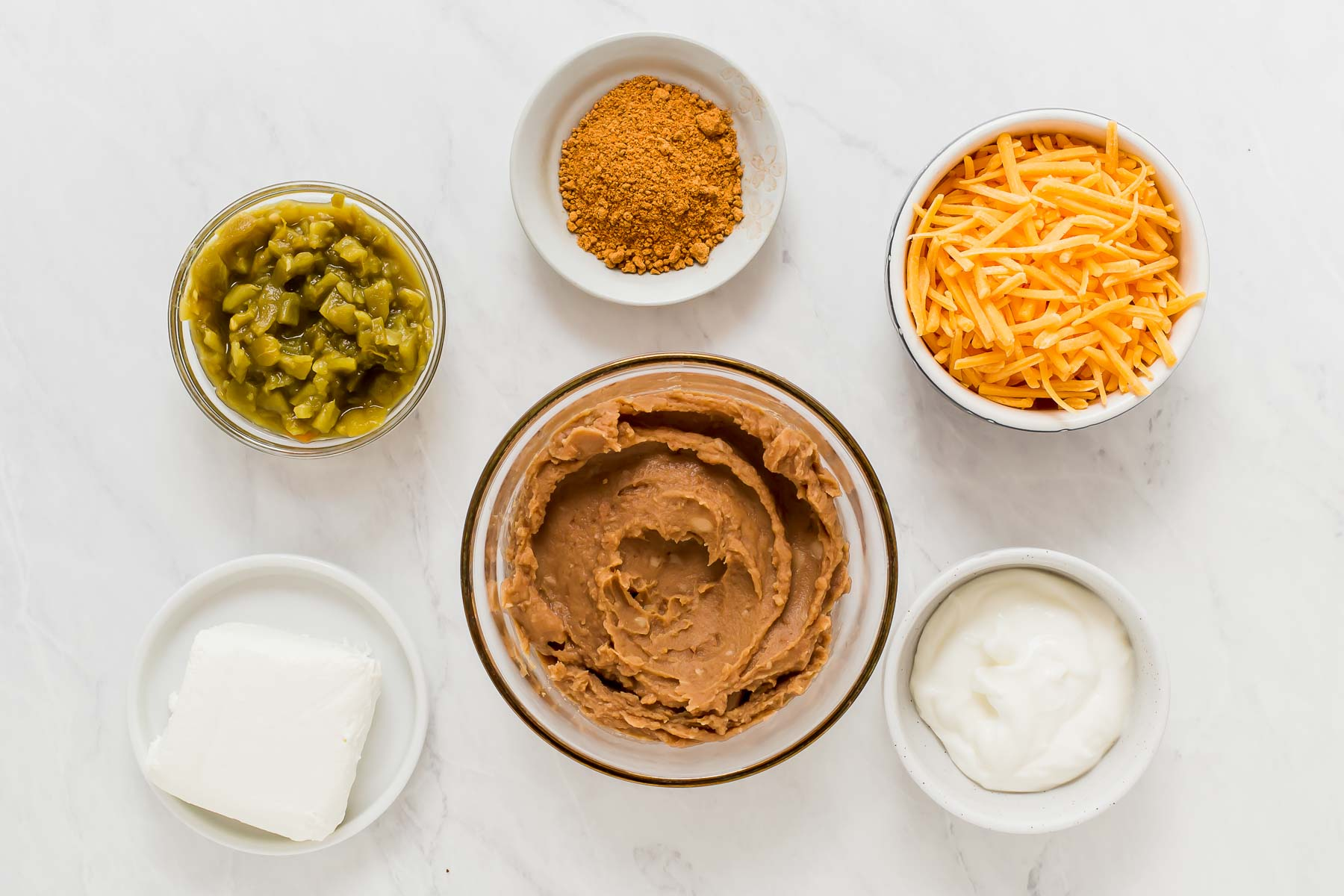 Bean dip ingredients in small bowls on white table.