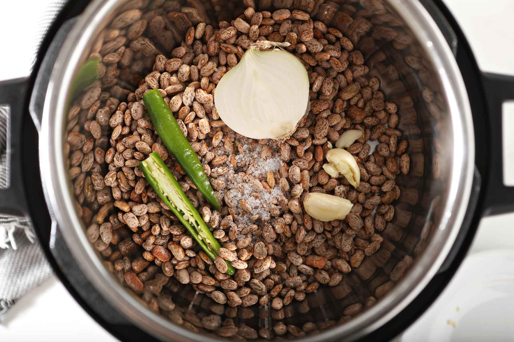 Pinto beans in instant pot with onions, garlic and pepper.