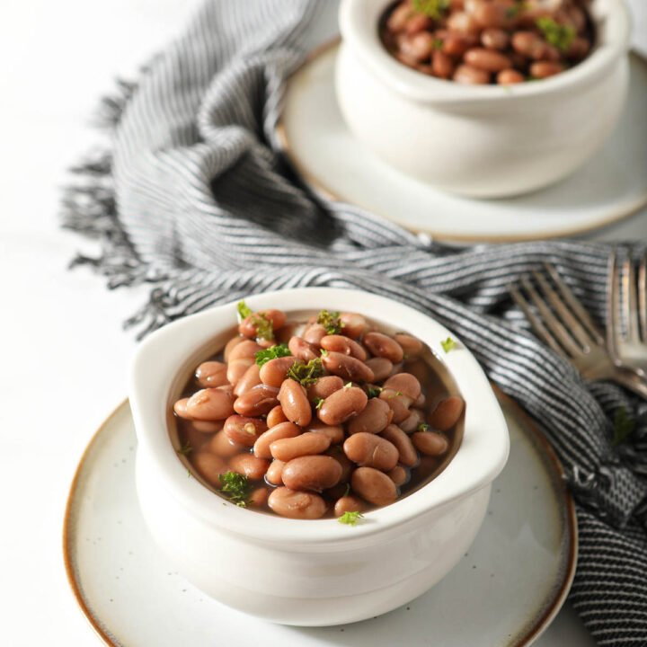 Two white bowls of pinto beans garnished with cilantro.