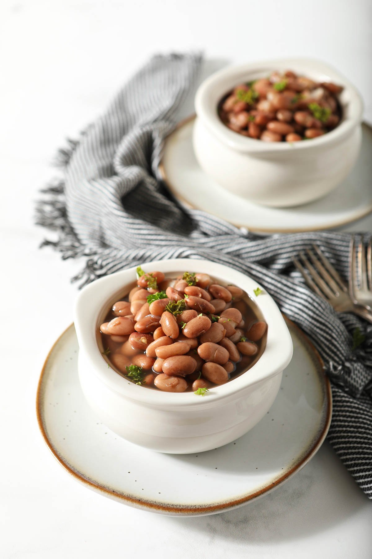 Two white cups of cooked pinto beans with napkin.
