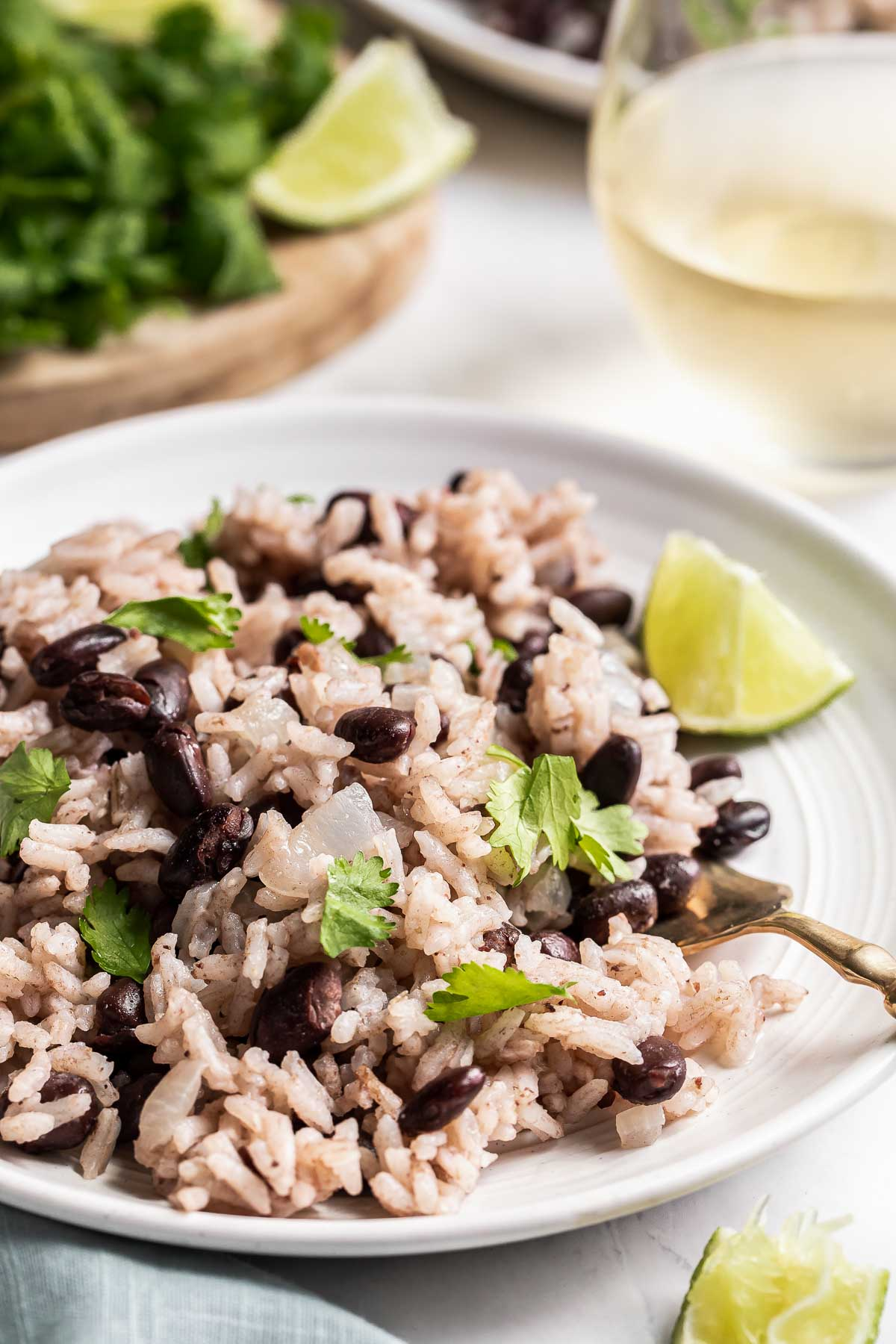 Close up of black beans and rice on plate with lime.