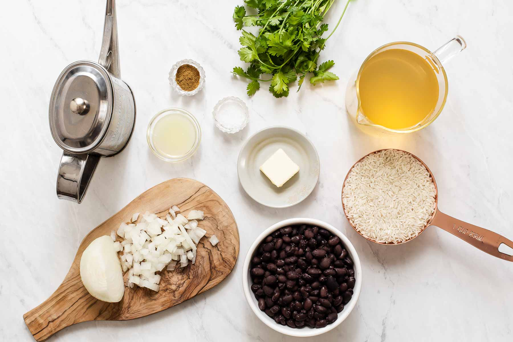 Ingredients for black beans and rice on white table.