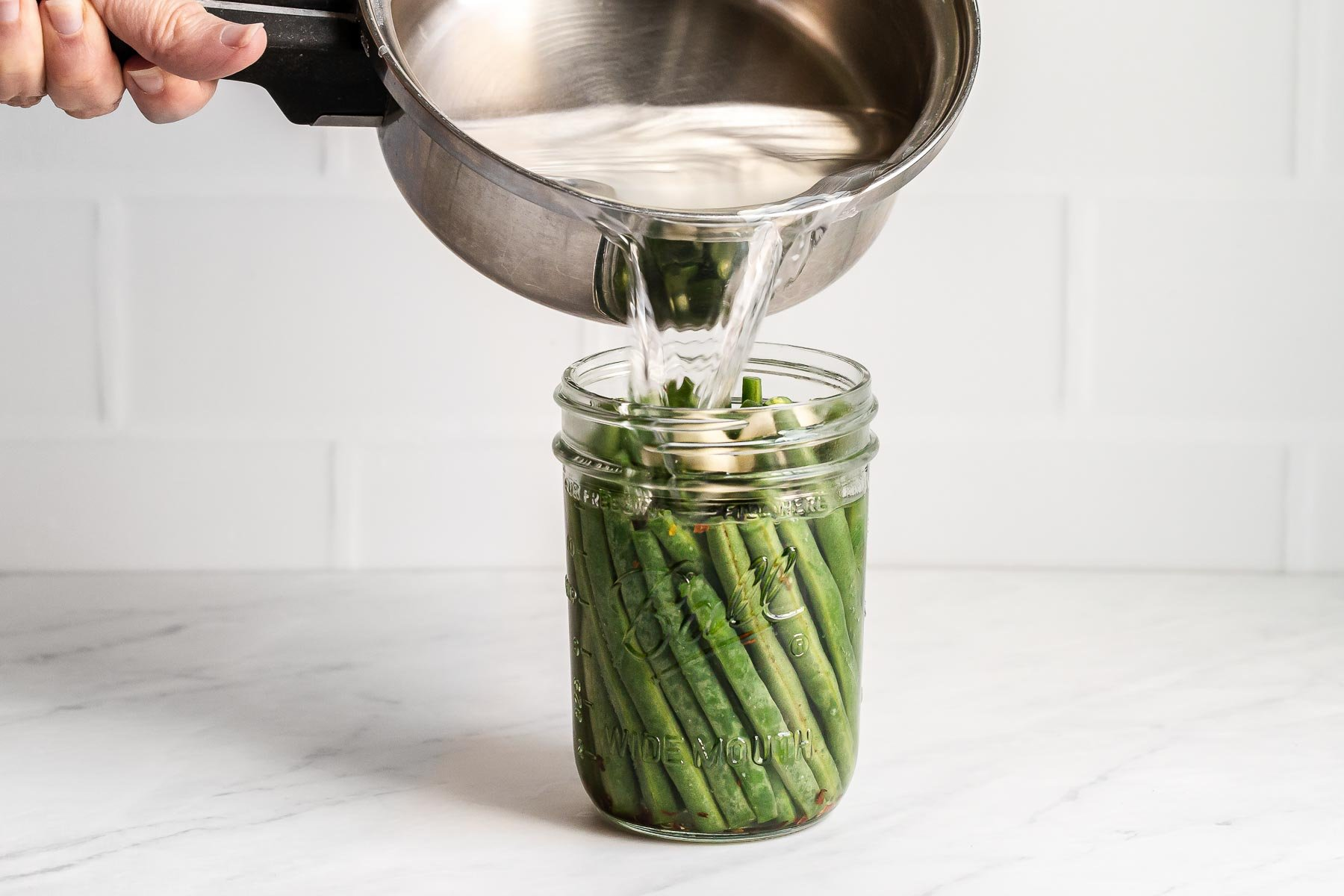 Pouring vinegar over green beans in a jar.