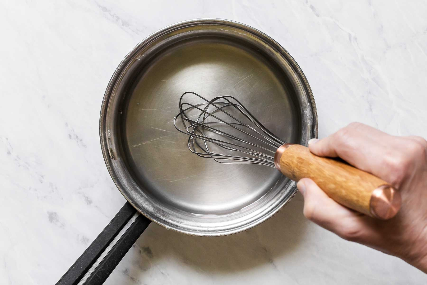 Water and vinegar boiling in pan with whisk.